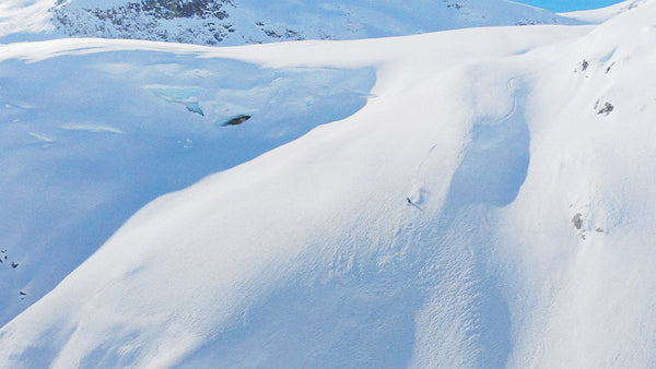 A skiier takes on a significant sheet of snow.