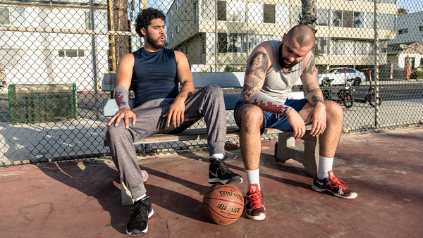 A pair of friends take a break from playing basketball, eSmartr sleeves on their arms.