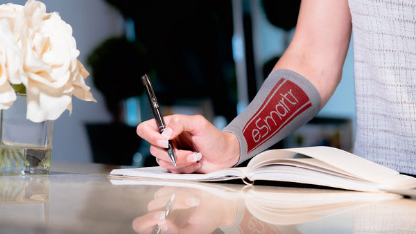 The eSmartr sleeve appears on an arm as it takes notes in an open notebook.