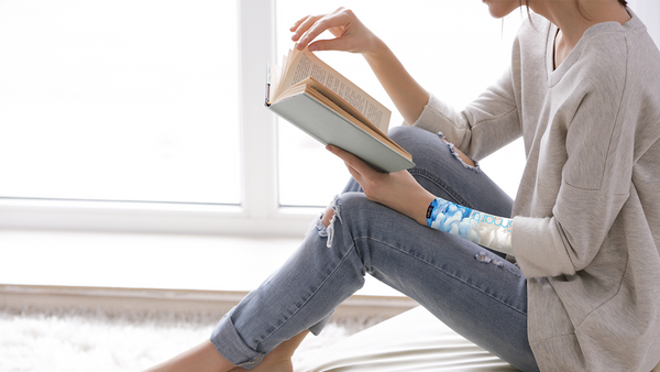 A young woman reads a book with an eSmartr smart compression sleeve on her arm to help her focus.