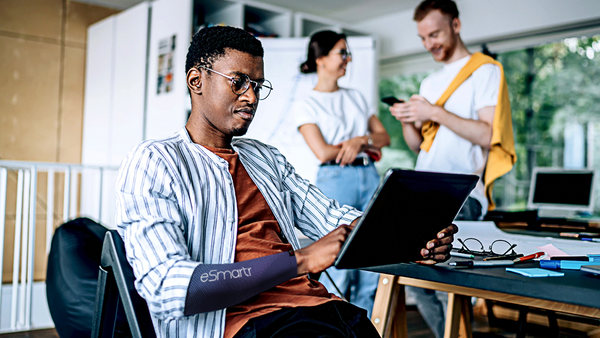 A man focuses on his tablet at work while two coworkers chat in the background.