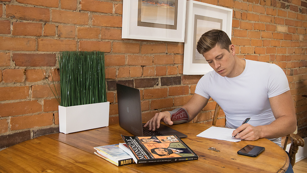 A young man has a lot to focus on at home for schoolwork as he takes notes near a laptop. He has an eSmartr smart compression sleeve on his arm.