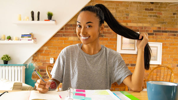 A young woman pauses while studying. She is using an eSmartr sleeve to improve her concentration as she works.