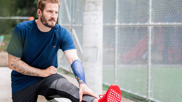 A man stretches before a run with an eSmartr sleeve on his arm.