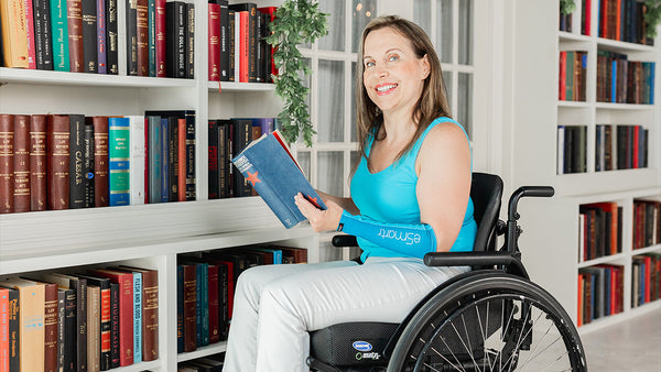 A woman browses through a bookshelf with eSmartr's smart compression sleeve on her arm.