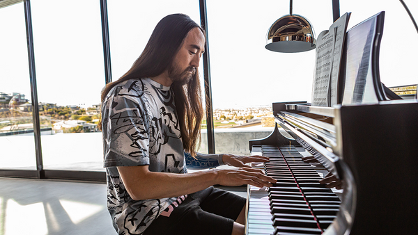 Steve Aoki plays piano with an eSmartr sleeve on his arm.
