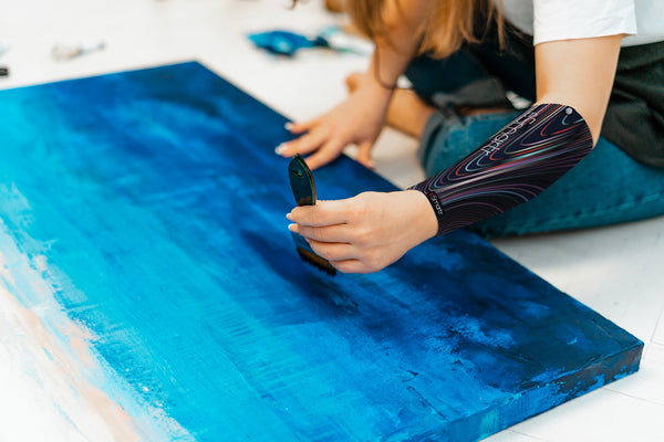 A woman paints blue on a canvas using a smart compression sleeve to help reduce cognitive stress.
