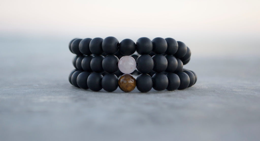 stack of athletic bracelets featuring different, natural, focal stones which are Onyx, Rose Quartz, Tiger's Eye