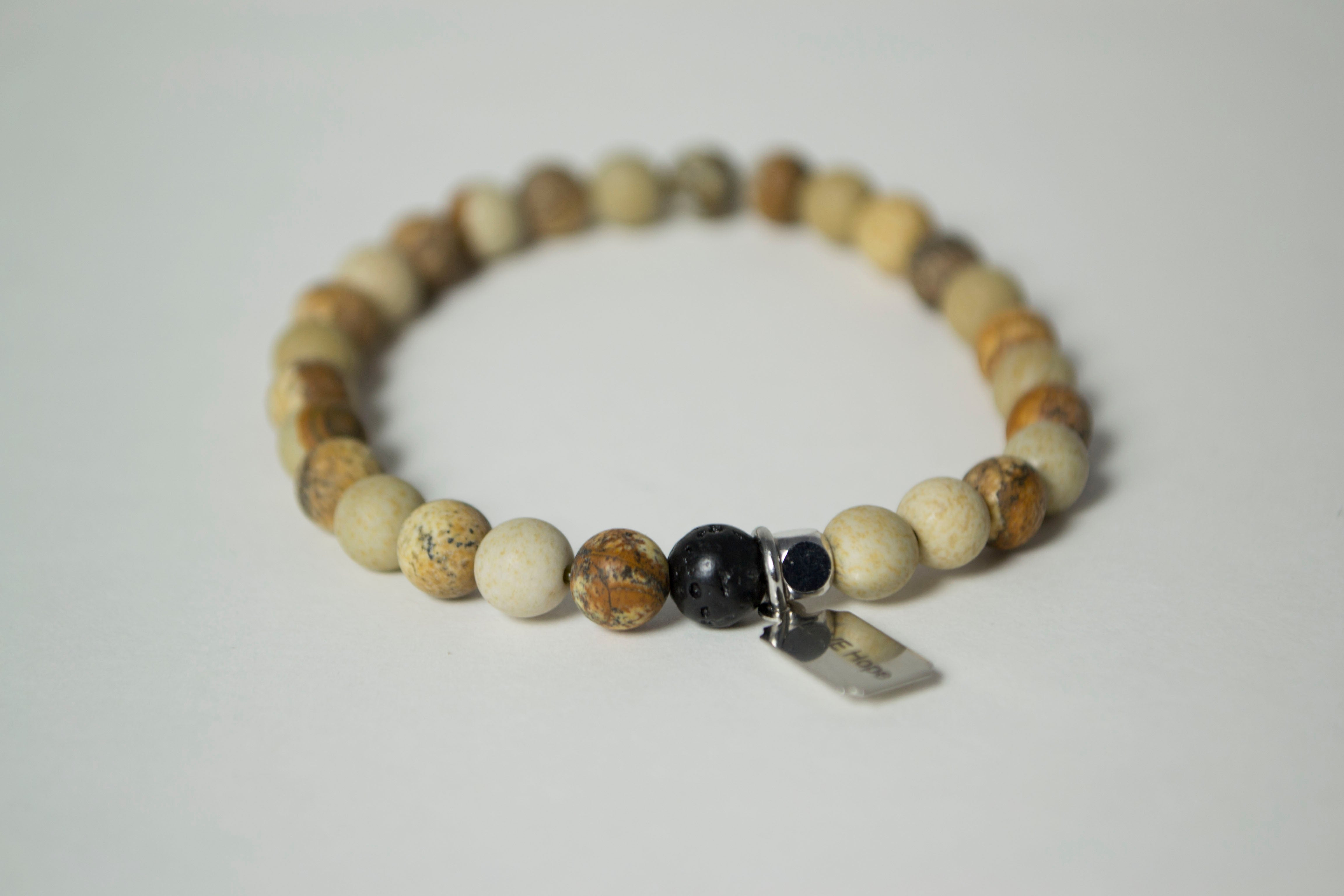 Rear view of the natural stones in the Infused Picture Jasper bracelet with details of the color and texture, including detail of the infusible Lava Stone bead. In the background is a blurred view of the front of the bracelet.