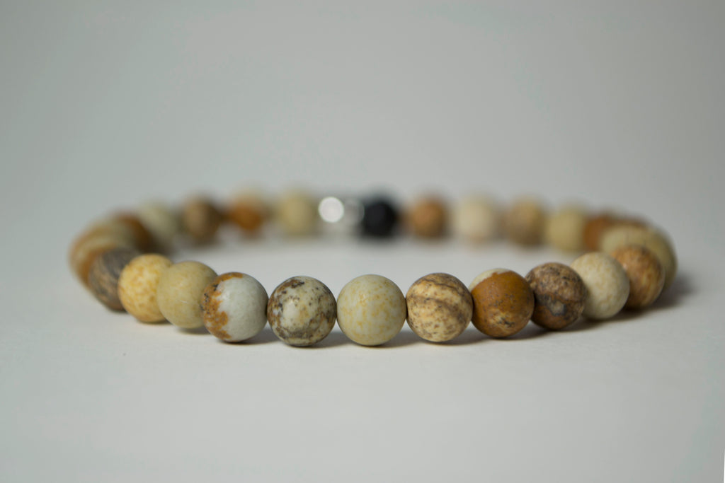 Front view of the natural stones in the Infused Picture Jasper bracelet with details of the color and texture. In the background is a blurred infusible Lava Stone bead
