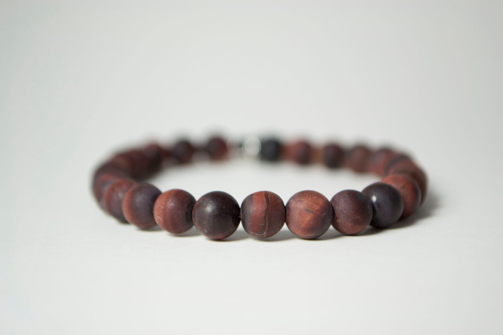 Front view of the natural stones in the Infused Red Tiger's Eye bracelet with details of the color and texture. In the background is a blurred infusible Lava Stone bead