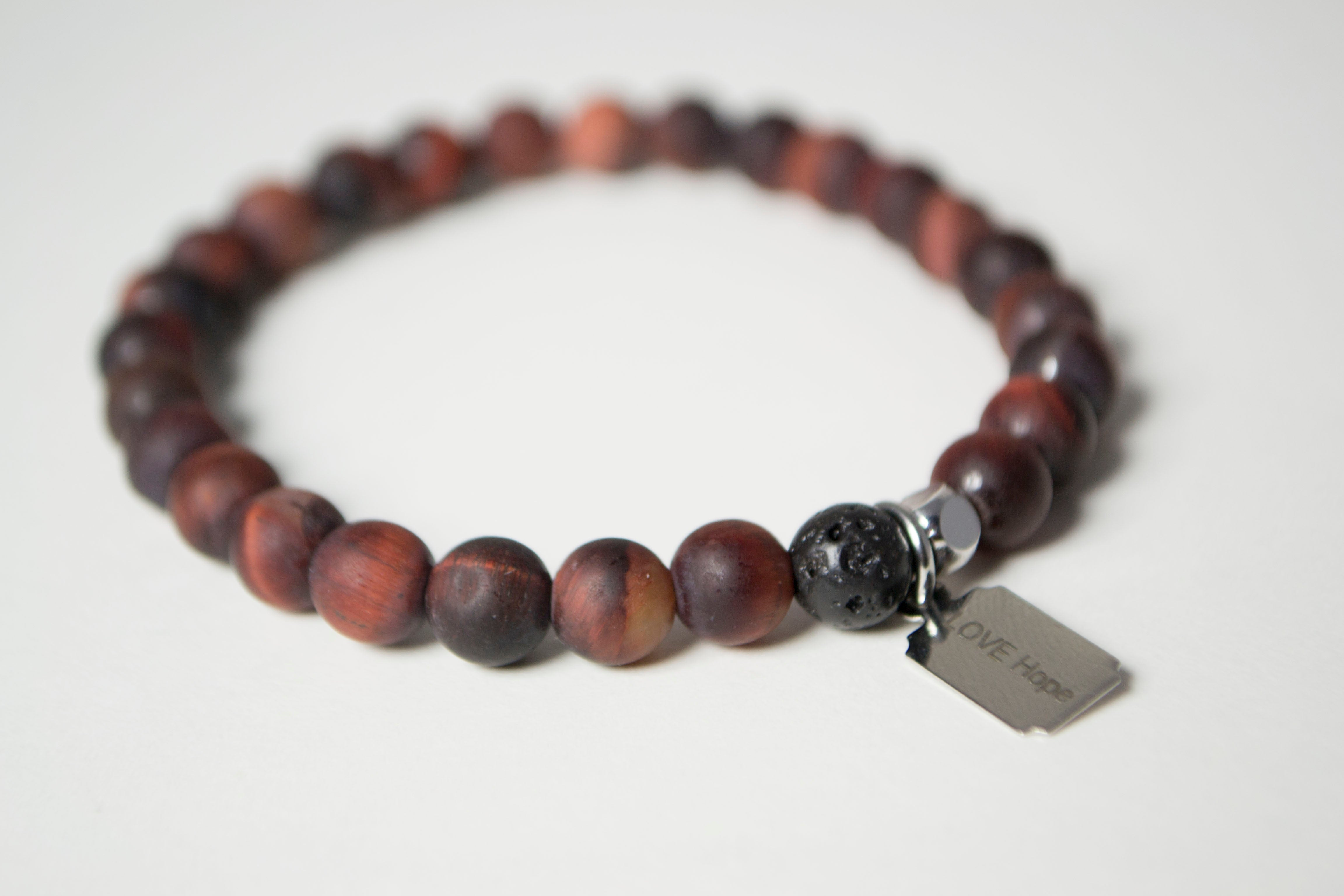 Rear view of the natural stones in the Infused Red Tiger's Eye bracelet with details of the color and texture of the infusible Lava Stone. In the background is a blurred view of the front of the bracelet