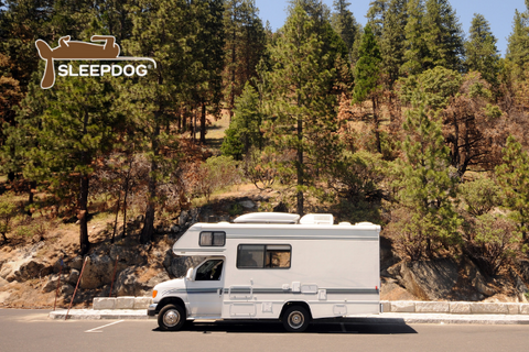 RV Camper parked in wooded parking lot
