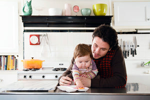 blog watch me bloom, recipes for growing me ~9 months, what is responsive feeding, close up of dad holding baby in kitchen, baby reaching for food on plate