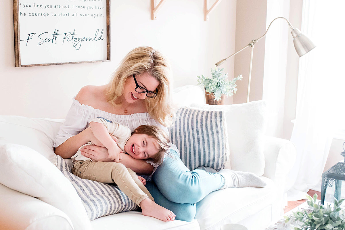 mom with blonde hair and black glasses tickling son on couch