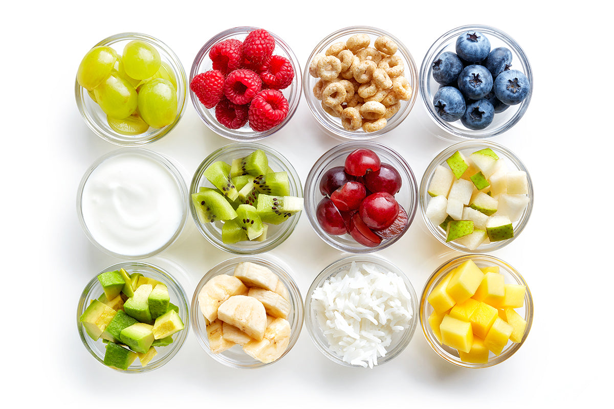 assortment of foods in baby finger bowls: green grapes, raspberries, cheerios, blueberries, yogurt, kiwi chopped, red grapes, green apple, avocado, banana slices, rice grain, mango