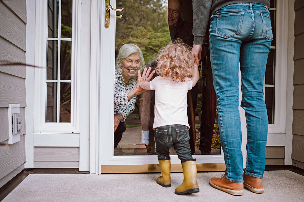 Parent and child with curly hair and yellow rainboots standing outside the front door, child's hand pressed against glass to touch kneeling grandmother's hand held in same position on inside, with grandfather in background.