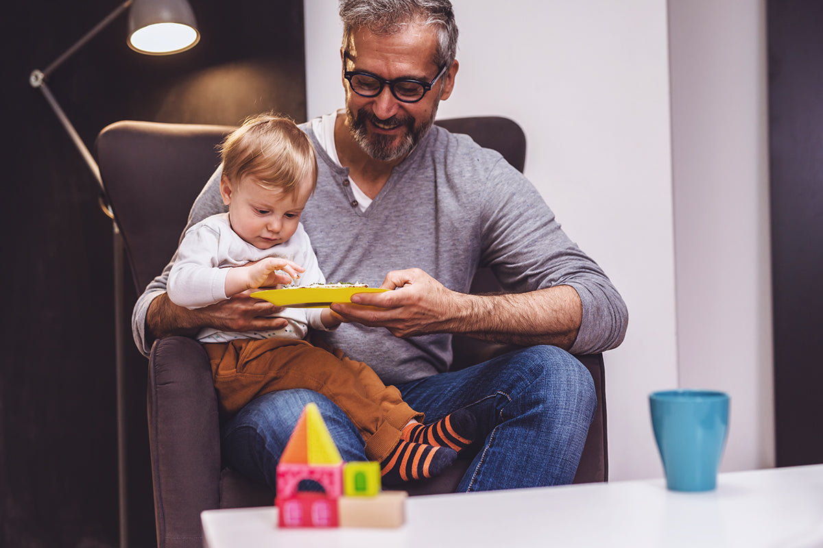 Young hip grandfather with black rimmed glasses sitting in armchair with grandson on lap dressed in rusty-coloured corduroy pants, and striped socks reaching for food on a bright yellow plastic plate grandfather is holding up.