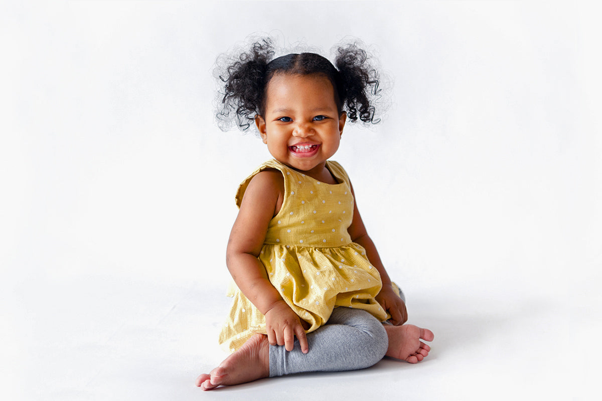 African American toddler smiling and dressed in yellow with grey tights, sitting on floor