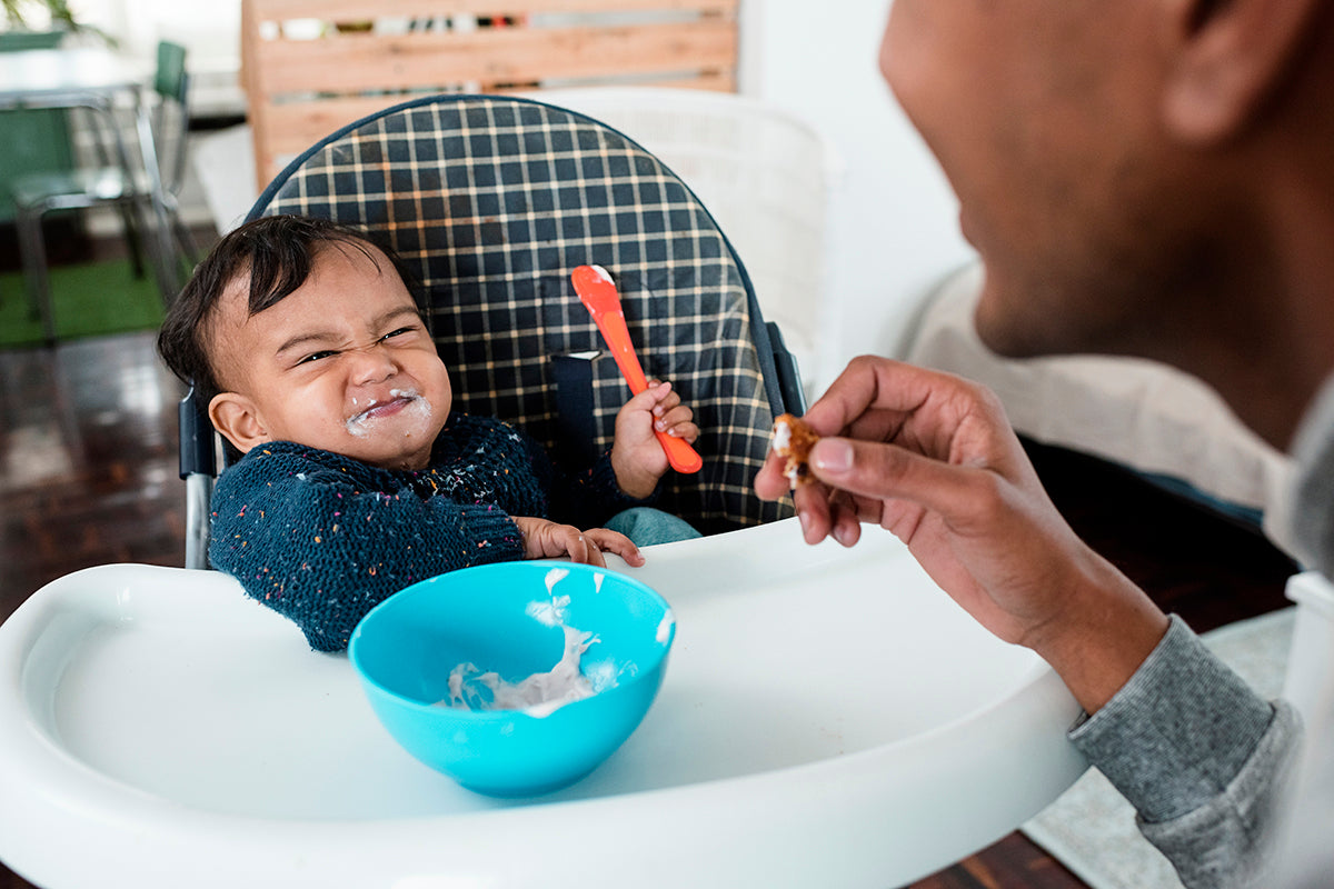 Indian baby boy in highchair holding spoon, with squishy facial expression, playful with Dad