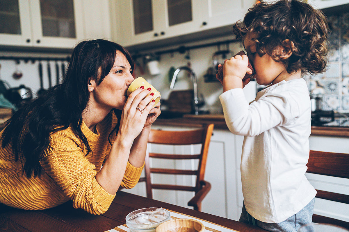 Mom mimics drinking from an open cup for her infant son learning to self-feed