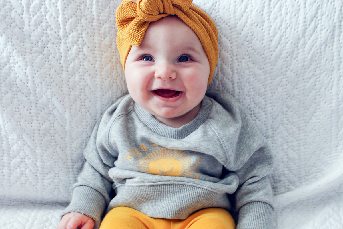 baby vitamin d supplement, happy baby girl with a sunshine sweatshirt, sitting up