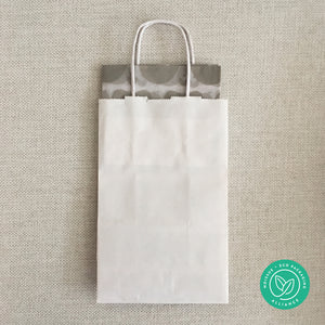 Sample white gift paper bag with folded sheets of warm grey heart patterned tissue inside