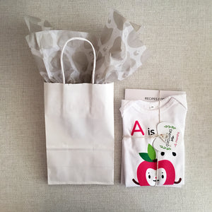 White paper gift bag, plain, with warm grey heart pattern tissue paper inside, shown next to baby shower bundle gift, baby's first A-Z cookbook tied together with matching A is for apple red character apple illustration on white onesie