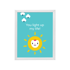 "Solid bright blue background, bright yellow sun happy face character illustration, encouraging message ""you light up my life"" in white lettering inside a sample white wood frame"
