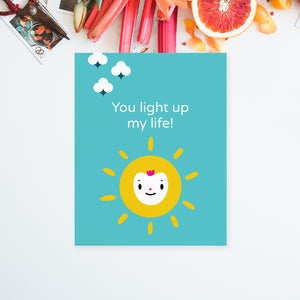 "Solid bright blue background, bright yellow sun happy face character illustration with encouraging message ""you light up my life"" in white lettering shown on 8.5x11 paper to download and print yourself"