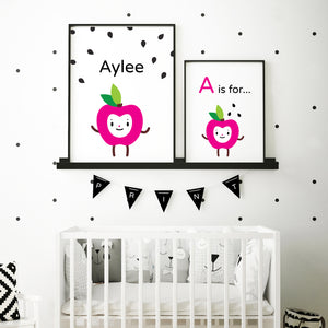 "Pair of illustration artwork in frames side by side, personalize a child's name on this adorable ""A is for Apple"" fuchsia happy face character surrounded with black apple seeds background, shown in sample baby's room above crib in black frame"