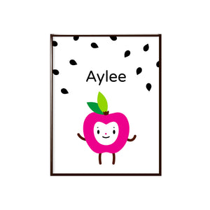 "Sample of personalized adorable fuchsia apple happy face character with name ""Aylee"" shown surrounded by black apple seeds background character illustration on white, shown in sample black metal frame"
