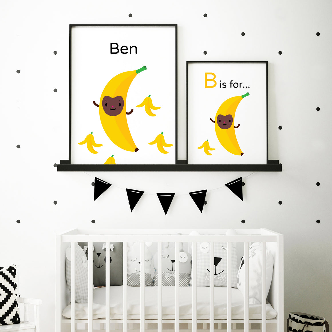 "Pair of illustration artwork in frames side by side, personalize a child's name on this bouncing ""B is for Banana"" yellow character with brown happy face character illustration surrounded by banana peels on white background, shown in sample baby's room above crib in black frame"