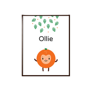 "Sample of personalized orange happy face fruit character with name ""Ollie"" in black lettering shown surrounded by green leaves illustration, shown in sample black metal frame on white background"