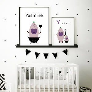 "Pair of illustration artwork in frames side by side, personalize a child's name on this baby ""Y is for yams"" purple character with happy face holding a heart balloon and sitting in a colander, illustration on white background, shown in sample baby's room above crib in black frame"