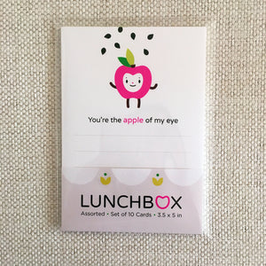 "sample front packaging of lunchbox cards, shown here fuchsia apple happy face character illustration on white background card ""you're the apple of my eye"", see through plastic wrapping, assorted"
