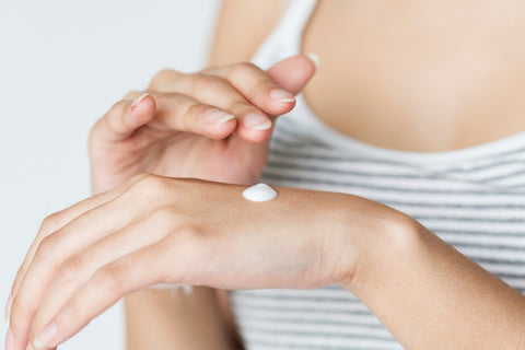Woman rubbing lotion onto hand