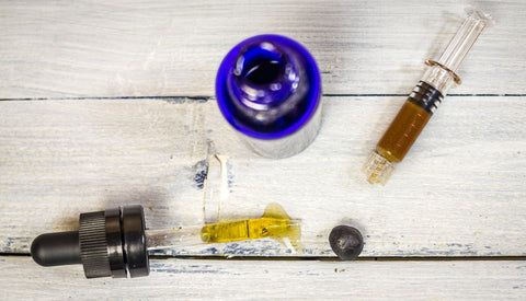 Oil Dropper and Syringe with CBD Paste inside of it laying on a wooden surface