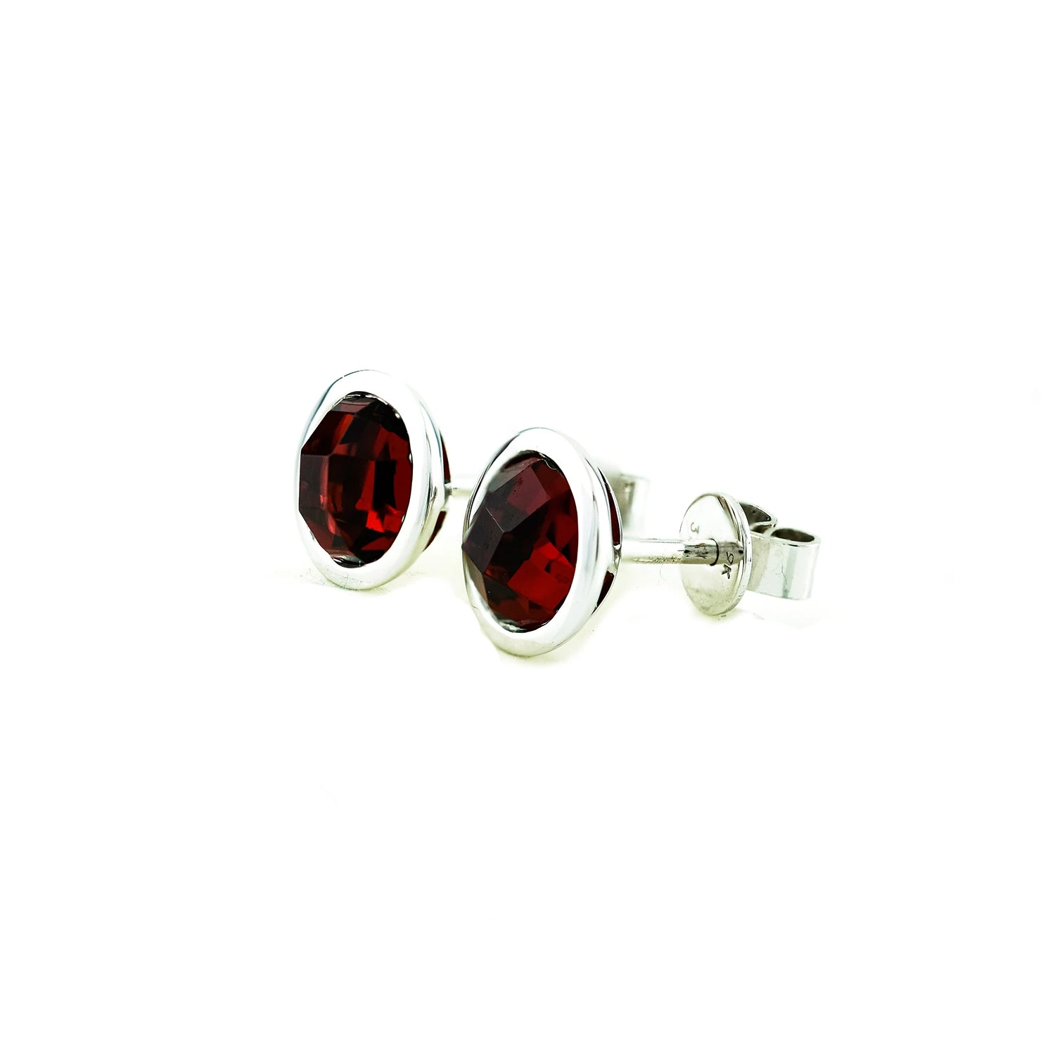 Stud earrings with a round red garnets rub over set into 9ct white gold.
