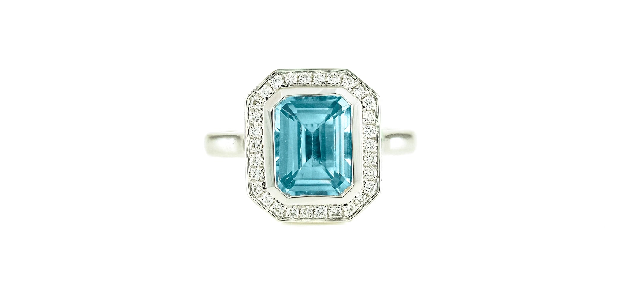 Art deco style emerald cut blue topaz surrounded by round brilliant cut diamonds on a 9ct white gold