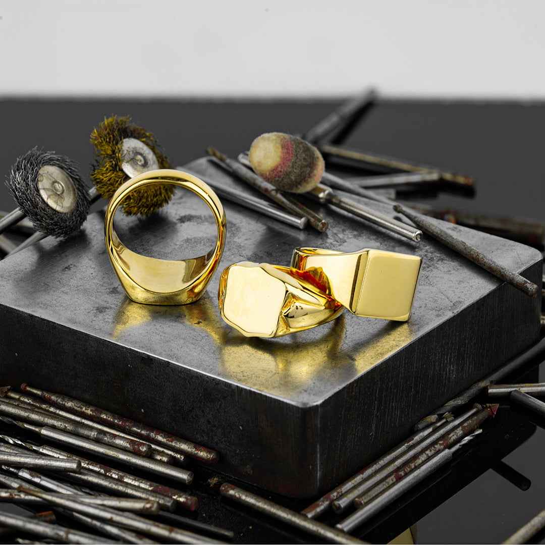 3 bespoke yellow gold signet rings surrounded by goldsmiths tools
