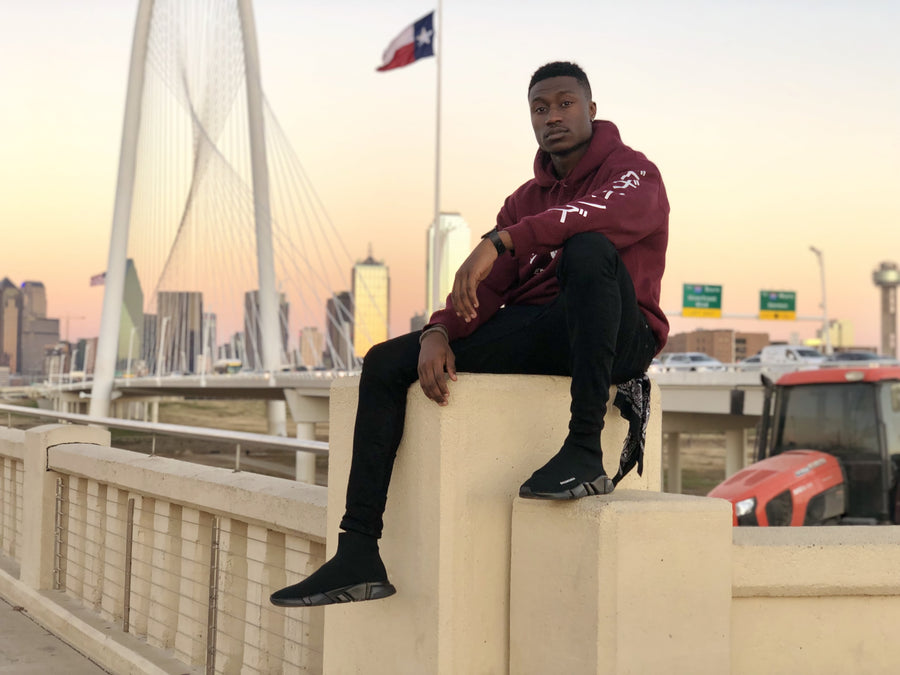 Dallas based startup company business with apparel clothing showcasing a brand. Maroon hoodie with screen printed designs downtown dallas texas.