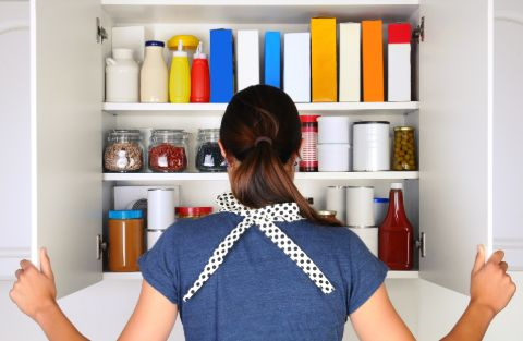 Woman looking in kitchen cabinet for at home mosquito repellent