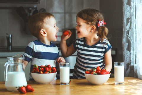 Two toddlers eating strawberries