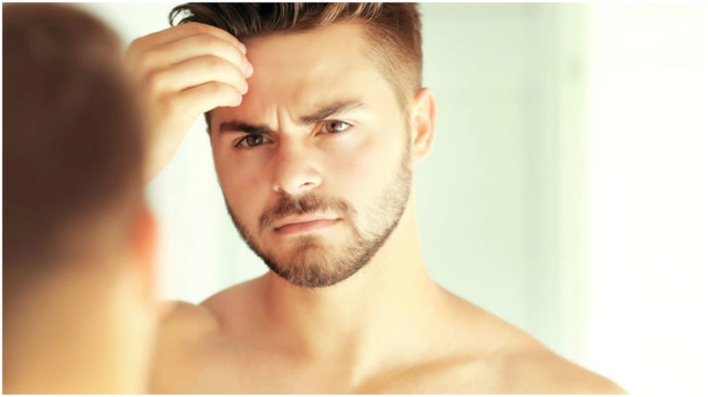 male grooming|man looking in mirror|man washing face|man grooming lifestyle|man with spot|man-looking-mirrow-clear-skin-chin-acne