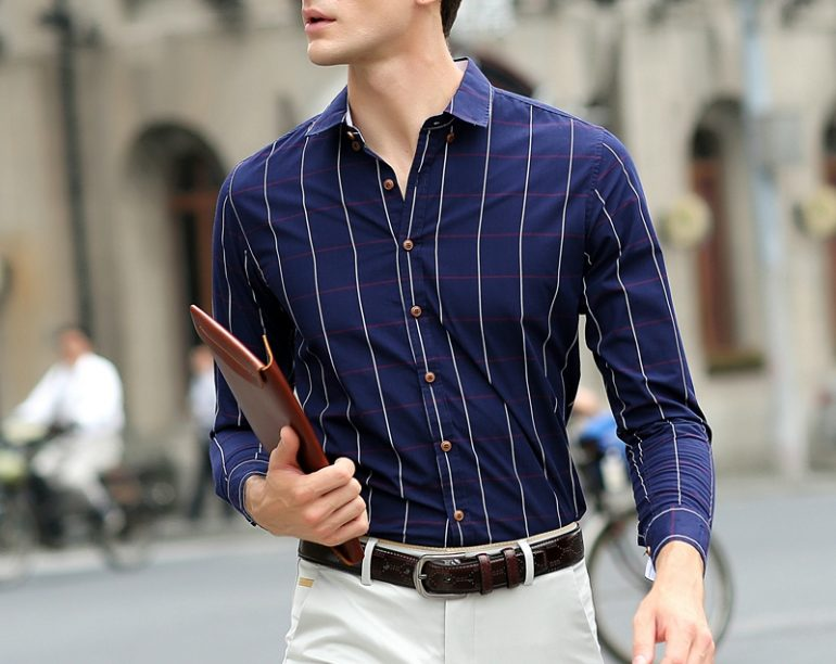 A man wearing a navy shirt and beige chinos