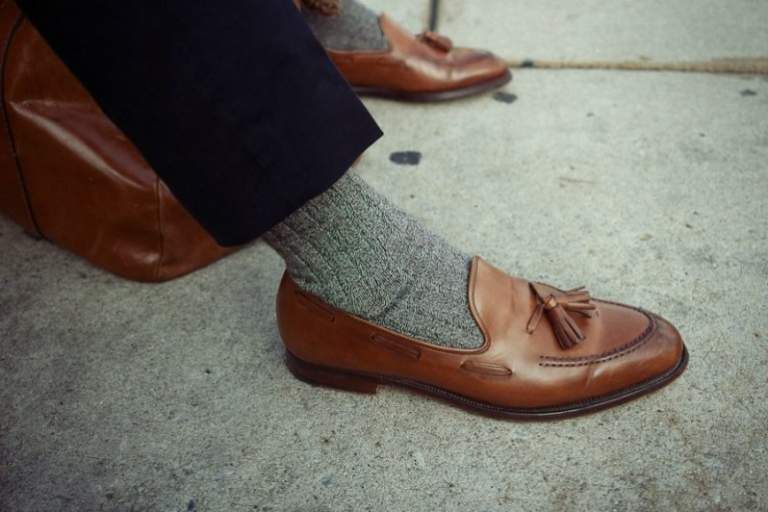 brown-loafers-on-foot-grey-socks-blue-trousers