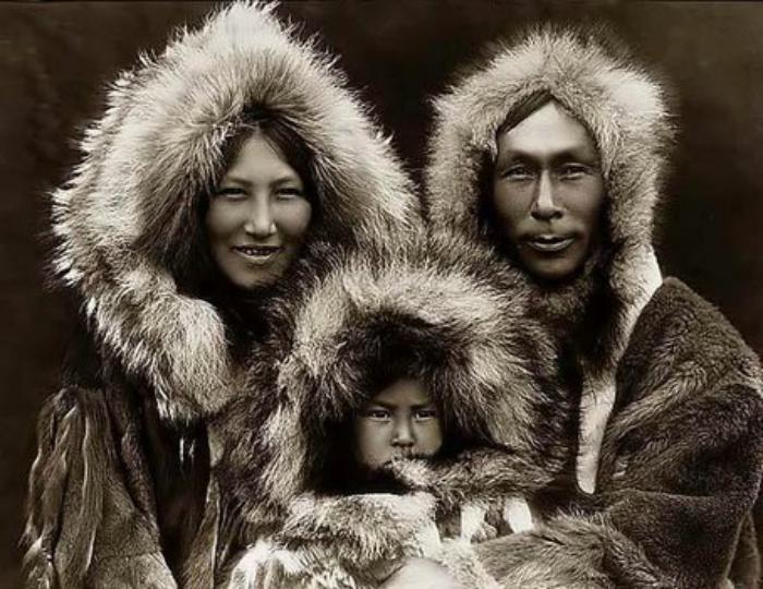 inuits wearing a traditional fur parka