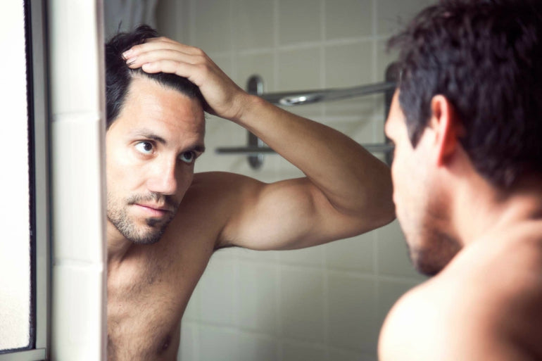 man checking hair in mirror