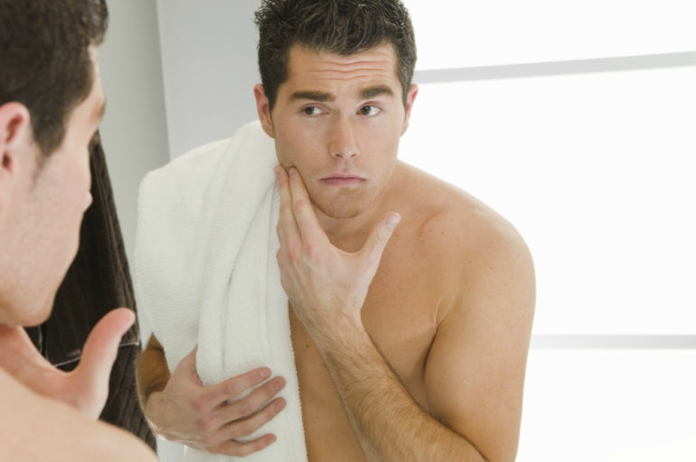 man looking in mirror washing face